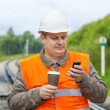 Stock Photo: Worker with cell phone and coffee on railway