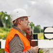 Worker with a coffee and cell phone on the railway in summer — Stock Photo