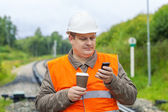 Worker with cell phone and coffee on the railway — Stock Photo