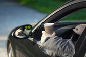 Man with coffee in car — Stock Photo