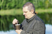 Man with coffee near river — Stock Photo