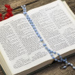 Bible with rosary on old boards — Stock Photo