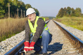 Railroad worker with adjustable wrench on railway — Stockfoto
