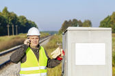 Railroad employee with cell phone near the electrical enclosure — Foto Stock