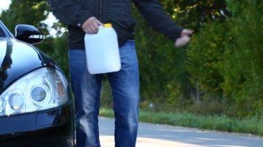 Adamın yanında yakıt teneke kutu bölüm 3 ile yolda araba — Stok video