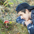 Boy in the forest watching fly agaric — Stock Photo