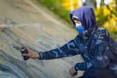 Teenager with color spray can near the wall — Stockfoto
