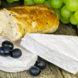 Stock Photo: Cheese with olives, grapes and bread on old wooden table