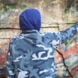 Stock Photo: Boy with color spray cnear wall