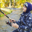 Boy fishing near river in autumn — Stock Photo