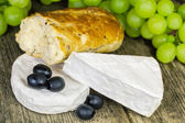 Cheese with olives, grapes and bread on old wooden table — Stock Photo
