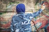 Menino com spray de cor pode perto da parede — Fotografia Stock