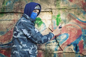 Teenager with color spray can near the wall — Stok fotoğraf