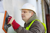 Builder with wash float near new building — Stock Photo