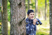 Teenager with binoculars in the woods — Stock Photo