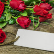 Red roses bouquet with blank sheet on wood — Photo