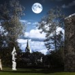 Full moon over an angel statue and castle ruins — Stock Photo