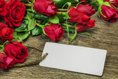 Red roses bouquet with blank sheet on wood — Stock Photo