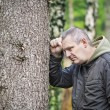Depressed man leaning on a tree episode 1 — Stock Photo