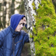 Sorrowful boy leaning on a tree — Stock Photo