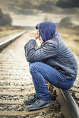 Sorrowful boy on the railway — Stock Photo