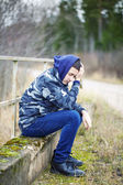 Sorrowful boy on the bridge near road — Stock Photo