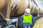 Railroad employee with folder near the tank wagons — Stock Photo