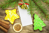 Two gingerbreads with spruce branches on old wooden table — Stock Photo