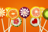 Lollipops in different colors on a orange background — Stock Photo