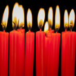 Burning candles in a row on black background — Stock Photo #37189809