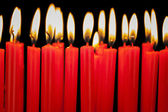 Burning candles in a row on black background — Foto Stock