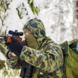 Stock Photo: Hunter with optical rifle and binoculars in woods