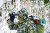 Hunter with binoculars and optical rifle in woods — Stock Photo