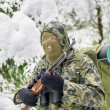Stock Photo: Hunter with binoculars and optical rifle in woods
