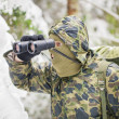 Stock Photo: Hunter with binoculars in forest in the winter