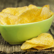 Stock Photo: Crispy potato chips in green bowl on wooden boards