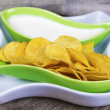 Stock Photo: Crispy chips in green bowl on wooden boards
