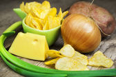 Chips with onion, cheese and potato on wooden boards — Stock Photo