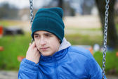 Sorrowful teenage boy swinging in the park — Stock Photo