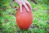 Hand on rugby ball on green grass background — Stock Photo
