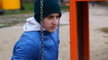 Sorrowful teenage boy swinging in the park episode 1 — Stock Video
