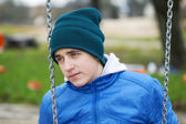 Teenage boy swinging in the park — Stock Photo