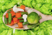 Vegetables on wooden spoon on lettuce — ストック写真