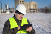 Engineer with tablet PC near the factory in winter — Stock Photo