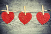 Three hearts hanging on a wooden boards background — Stock Photo