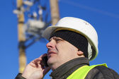 Electrical Engineer with cell phone near transformer — Stock Photo