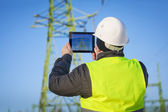 Electrical Engineer with tablet PC near High voltage tower — Stock Photo
