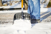 Man with a snow shovel on the trails — Stock Photo