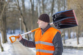 Man with a snow shovel on the sidewalk — Stock Photo