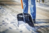 Man with snow shovel cleans sidewalks in winter — Stock Photo